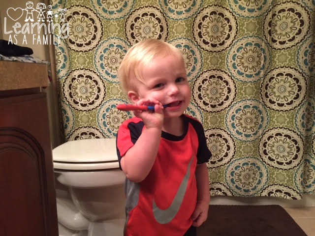 Toddler brushing his own teeth with Toddler with Nuby All Natural Toddler Training Toothbrush & Toothpaste