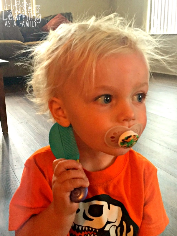 Toddler using comb from Nuby Brush and Comb Set